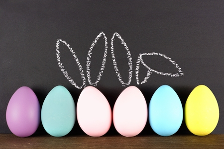 95360440 - row of easter eggs against a chalkboard background. two with hand drawn easter bunny ears.