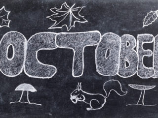 52727972 - handwritten october with autumn symbols, leaves, mushrooms and squirrel on black chalkboard